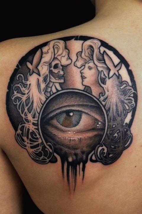 Illustrative style colored shoulder tattoo of woman portraits and human eye