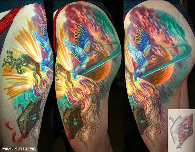 Illustrative style colored thigh tattoo of flying fantasy bird and planet