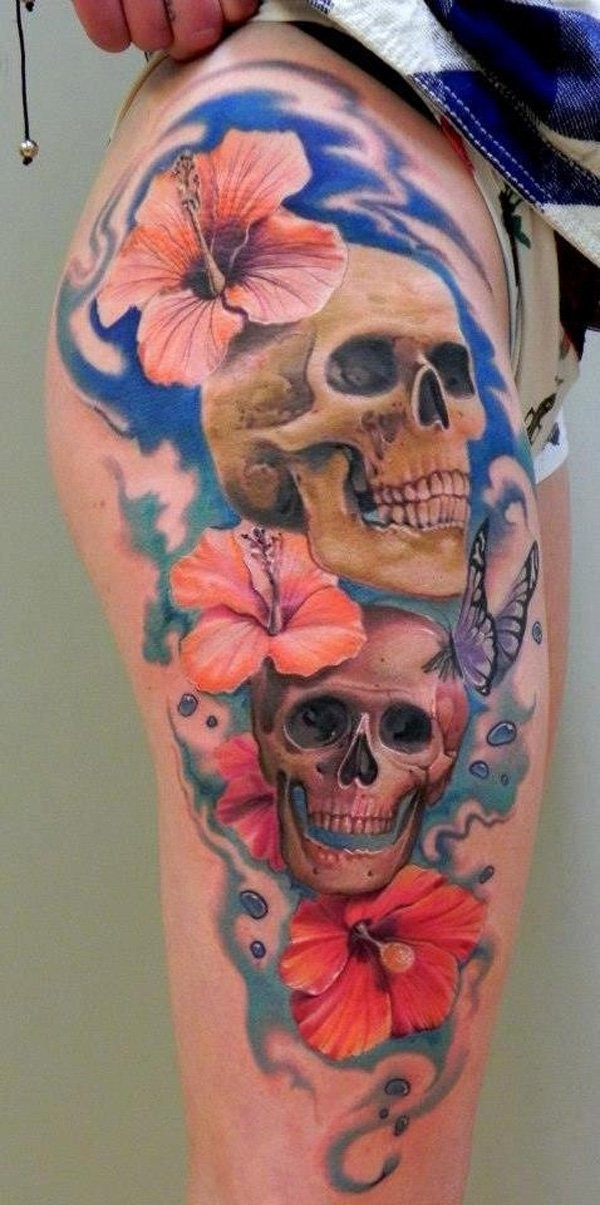Illustrative style colored thigh tattoo of human skulls with flowers and butterflies