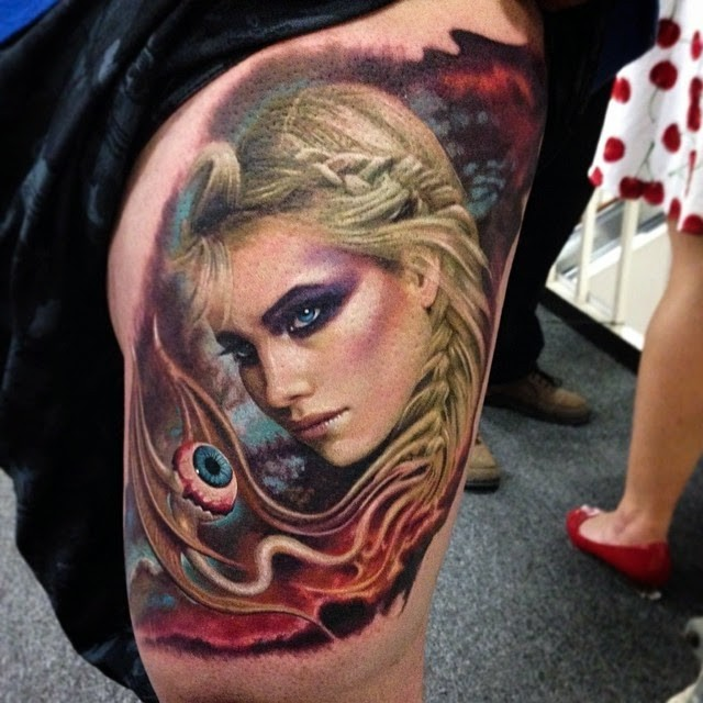Illustrative style colored thigh tattoo of fantasy woman with creepy eye