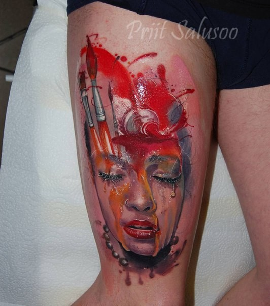 Illustrative style colored thigh tattoo of woman face with paint and brushes