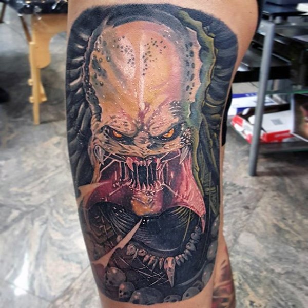 Illustrative style colored thigh tattoo of creepy Predator face