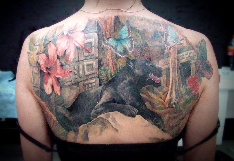 Illustrative style colored upper back tattoo of black panther in deep jungle