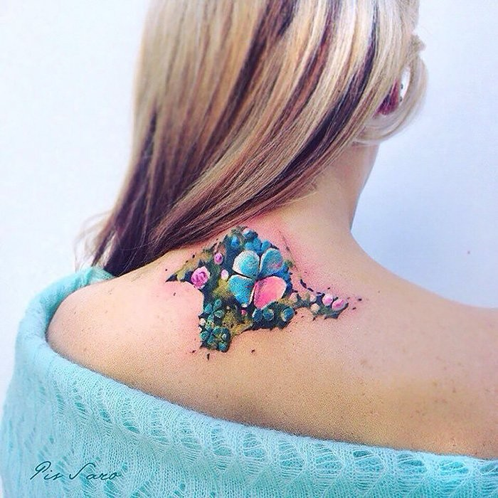 Illustrative style colored upper back tattoo of little flowers