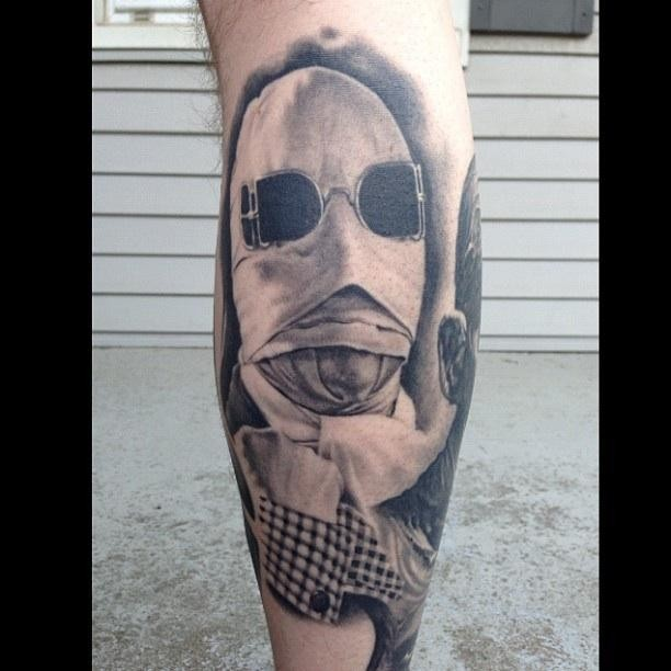 Impressive black and white realism style leg tattoo of masked man with sun glasses