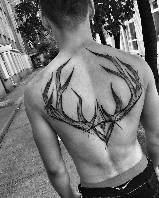 Impressive blackwork style upper back tattoo of deer horns