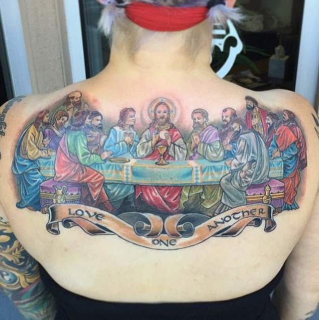 Impressive colored Lord&quots Supper tattoo on upper back with lettering