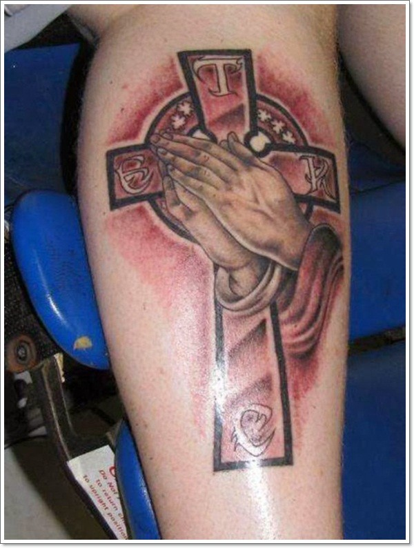 Impressive designed praying hands with mystical cross tattoo on leg