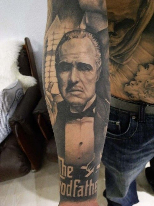 Impressive natural looking black ink God Father portrait tattoo on forearm with lettering