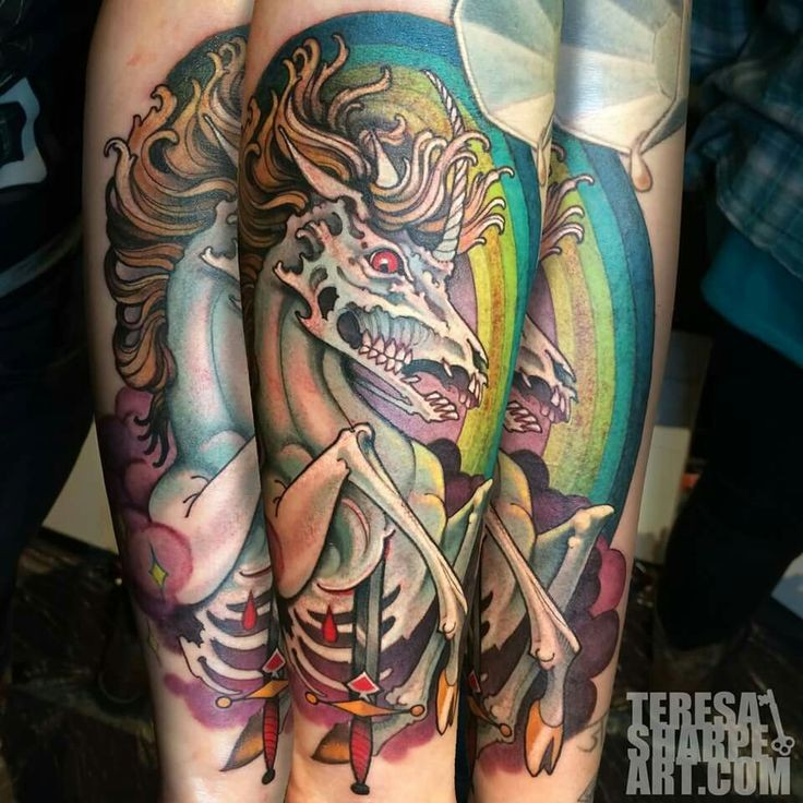 Impressive old school colored zombie unicorn tattoo on forearm with bloody sword
