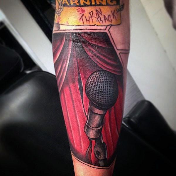 Impressive vintage like little microphone on stage tattoo on arm