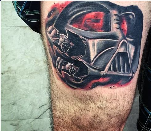 Incredible cartoon style colored big thigh tattoo of Darth Vaders mask with space ships