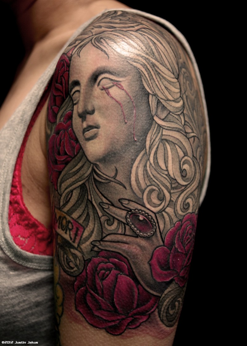 Incredible colored crying with bloody tear antic statue tattoo on shoulder stylized with flowers and lettering
