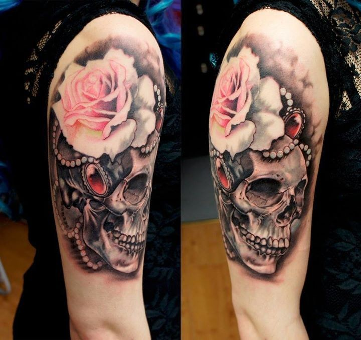 Incredible multicolored shoulder tattoo of human skull and flowers with jewelry