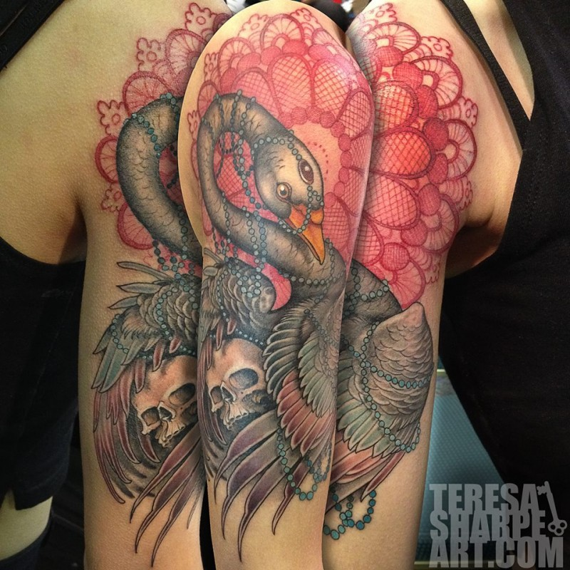 Incredible very detailed bird tattoo on shoulder with human skull and ornamental flower
