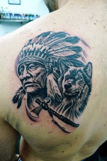 Indian chief with wolf and tomahawk tattoo on shoulder blade