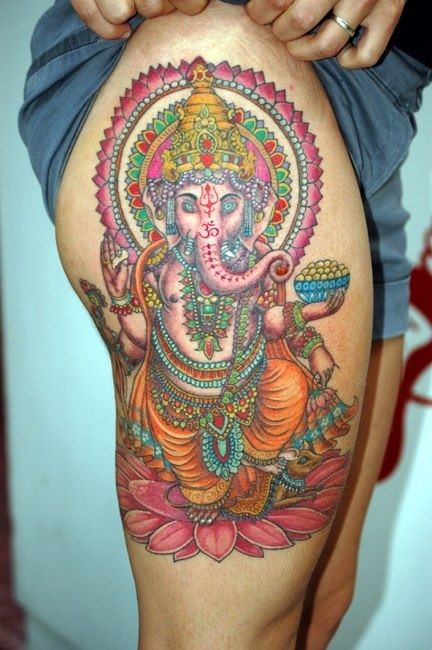 Indian ganesha on a lotus flower tattoo on thigh