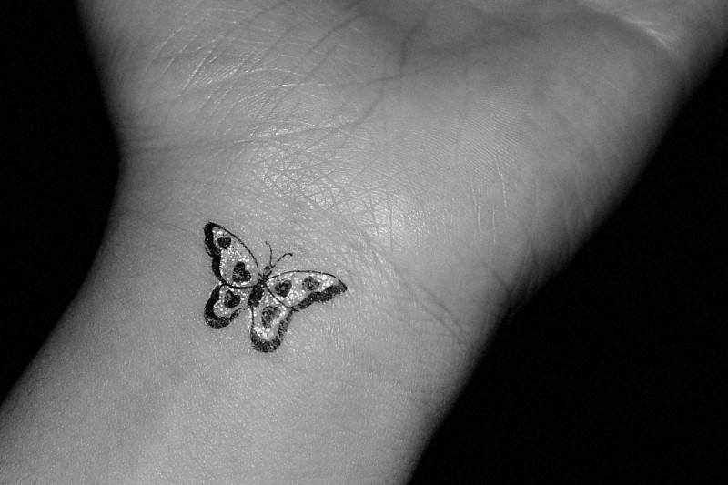 realistica piccola farfalla tatuaggio su polso