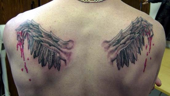 Interesting colored bloody broken wings tattoo on upper back