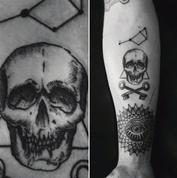 Interesting combined black and white skull with keys tattoo on arm