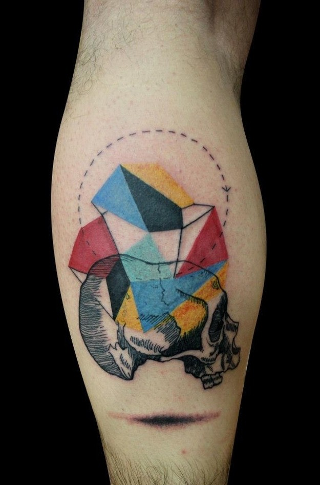 Interesting combined colored geometrical figures tattoo on leg muscle with human skull