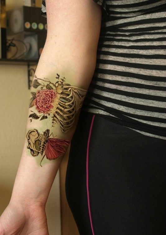 Interesting combined colored realistic skeleton with flowers tattoo on arm