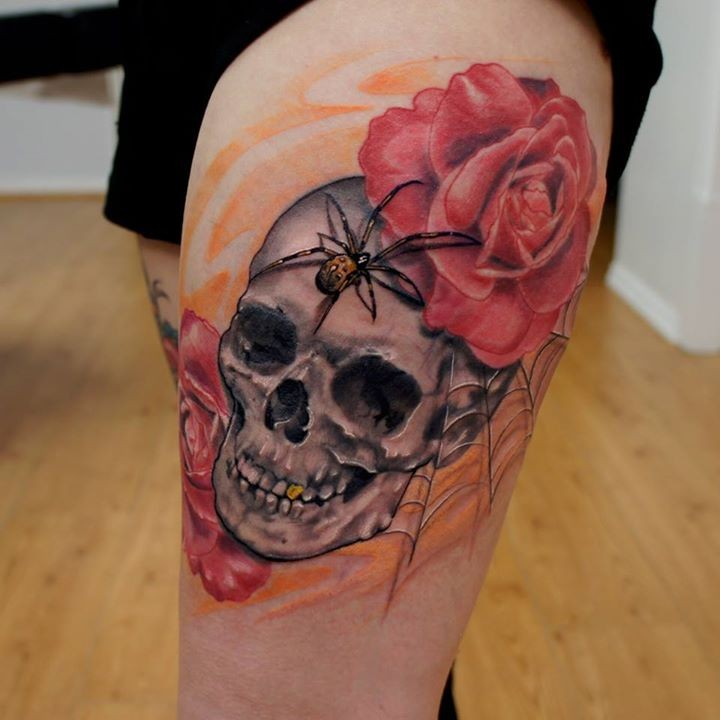 Interesting combined colored rose flowers tattoo on thigh combined with human skull and spider