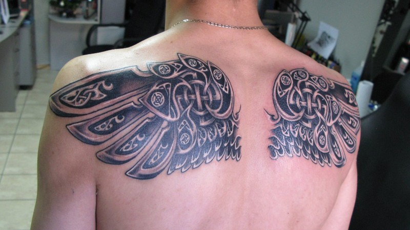 Interesting design pair of wings with Celtic symbols upper back tattoo