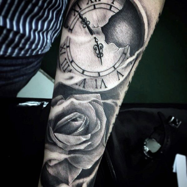 Interesting designed black and white clock with flower tattoo on sleeve