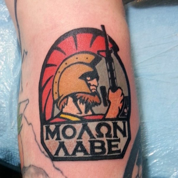 Interesting emblem like colored roman warrior with modern rifle and lettering tattoo on arm