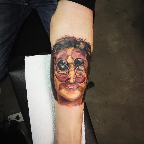 Interesting looking colored forearm tattoo of human face with sun glasses