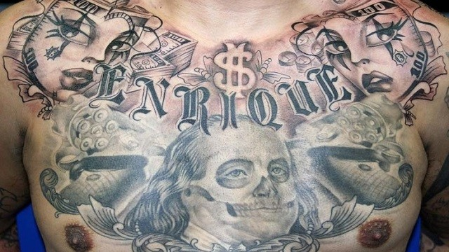 Interesting looking colored money bills tattoo on chest with lettering