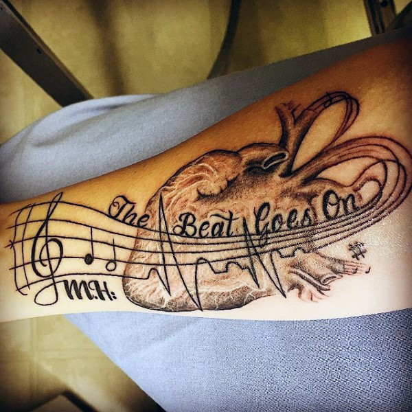 Interesting music themed black ink notes with lettering and heart tattoo on arm