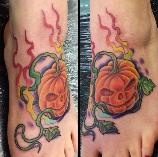 Interesting painted little cartoon pumpkin tattoo on foot