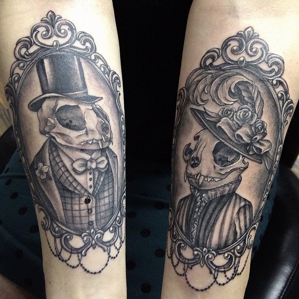 Interesting painted vintage style forearm tattoo of human portraits with animal skulls