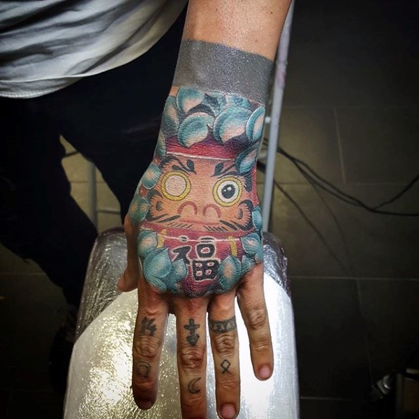 Japanese style colored hand tattoo of daruma doll with lettering and chrysanthemum