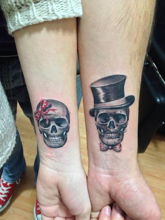 Tatuaggio carino sui bracci il teschio maschile e il teschio femminile