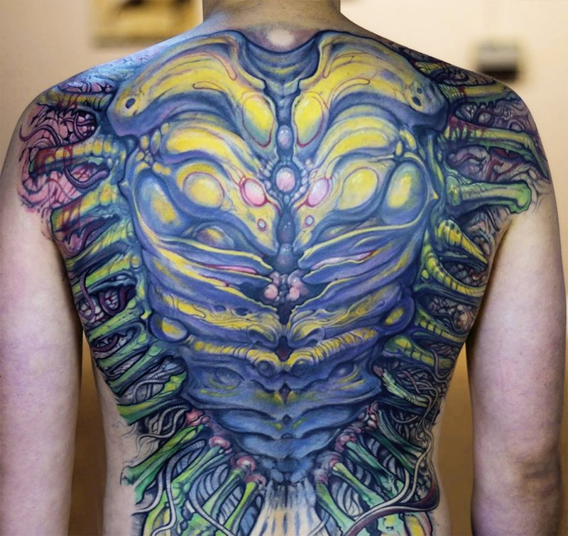 Large beautiful looking colored whole back tattoo of alien bones