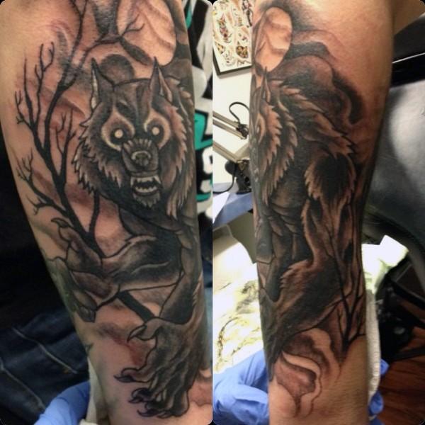 Large black and white leg tattoo of werewolf in dark forest