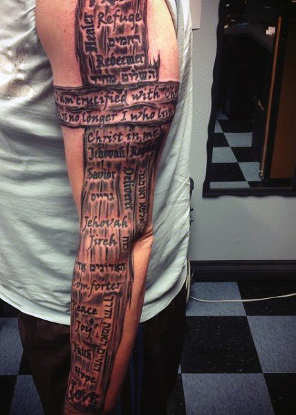 Large black in wooden cross tattoo on sleeve with lettering