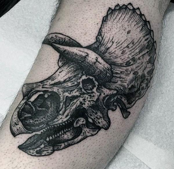Large black ink engraving style antic dinosaur skull tattoo on leg muscle