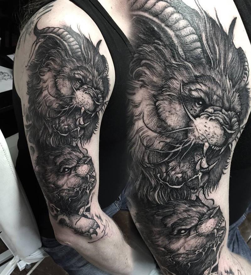 Large black ink mystical lion with goat horns tattoo on shoulder