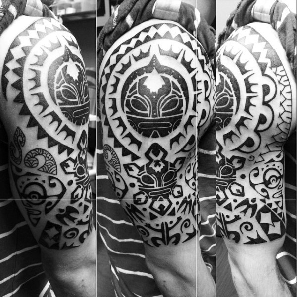 Large black ink Polynesian style tattoo on shoulder