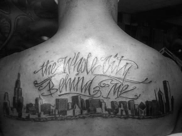 Large black ink upper back tattoo of city sights and lettering