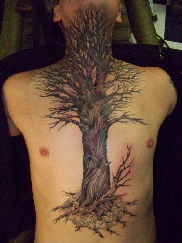 Large black tree and skull tattoo on chest and abdomen