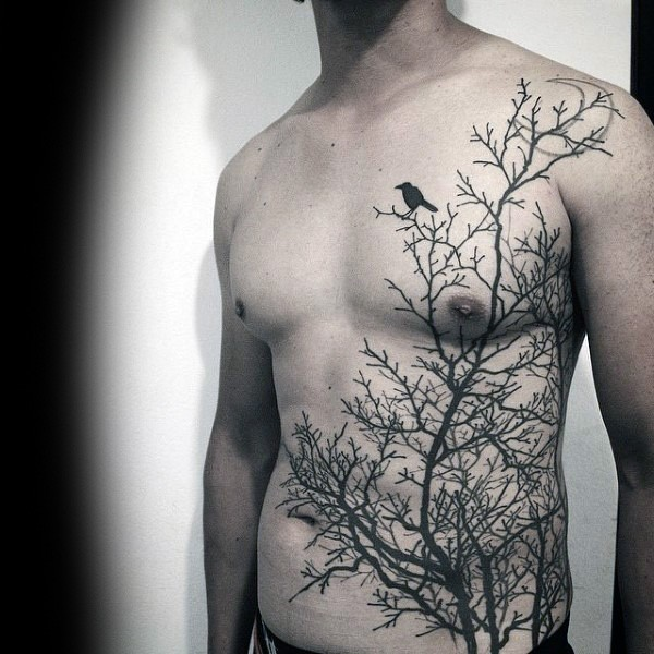 Large blackwork style chest and belly tattoo of dark forest and crow
