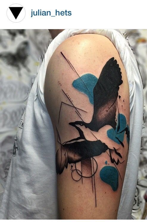 Large colored abstract style shoulder tattoo of flying bird