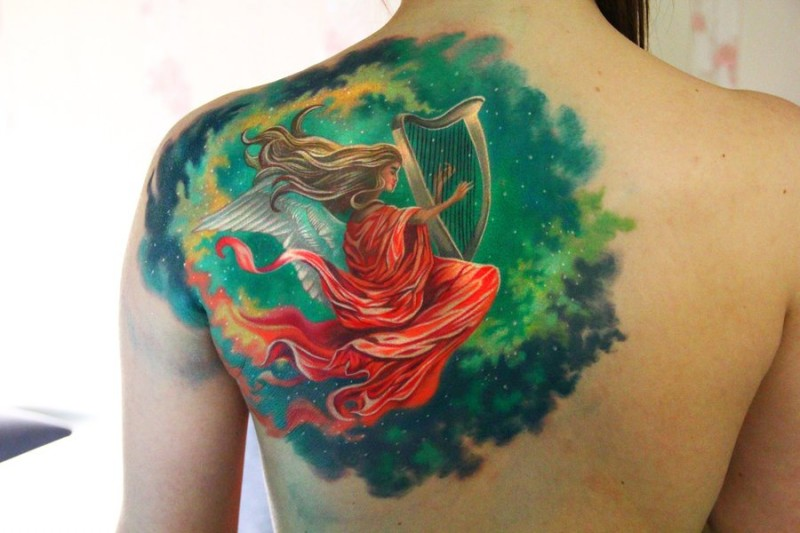 Large colored shoulder tattoo of illustrative style woman with harp