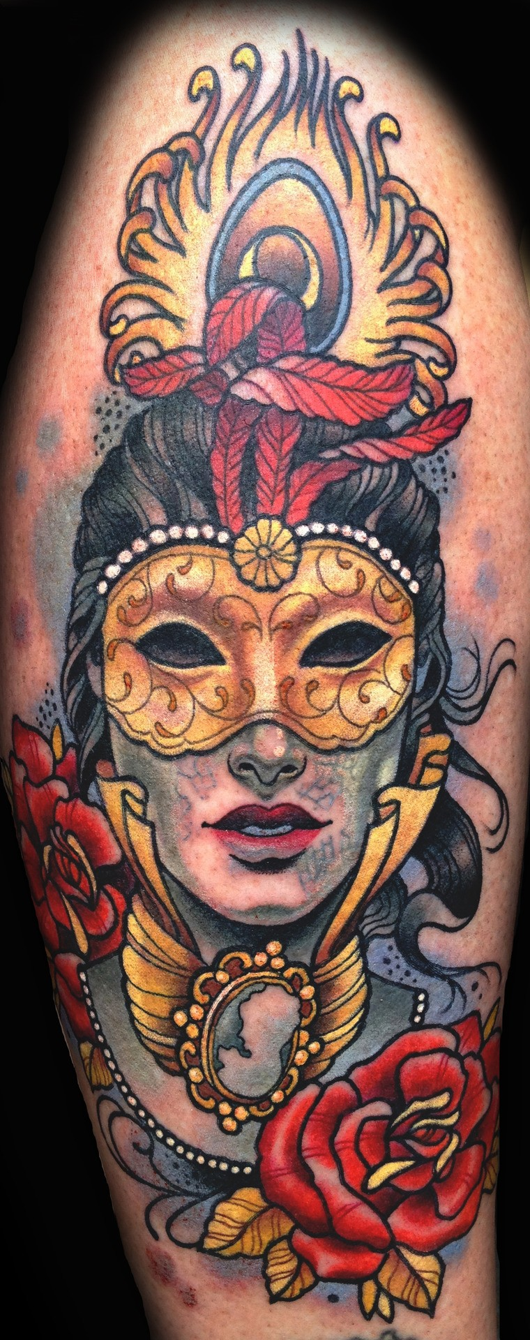 Large colored shoulder tattoo of mystical man with mask and feather