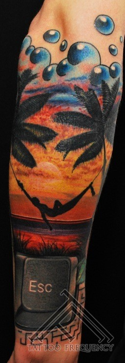 large colorful forearm tattoo of human on beach with palm trees